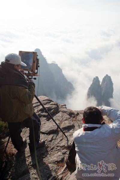 两个牛人在黄山群峰顶栏杆外在拍摄,相当危险.jpg